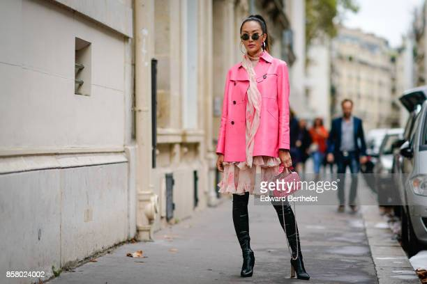 Chriselle Lim wears sunglasses a pink jacket a pink skirt black thigh high boots a pink bag outside Valentino during Paris Fashion Week Womenswear...