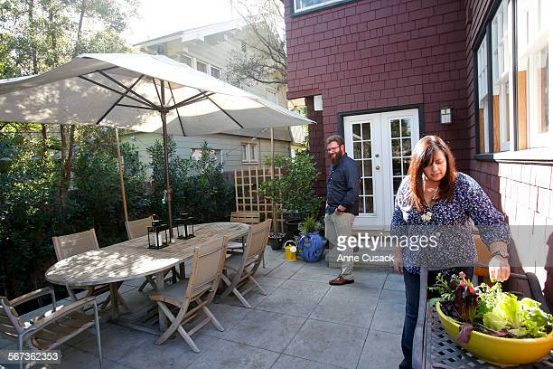 Chrisi Echiverri tends a lettuces growing in a pot as Michael Cimarust walks toward the outdoor dining area where the family often dines at the home...