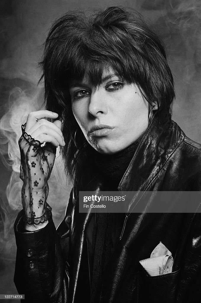 Chrissie Hynde, US singer and guitarist with rock band The Pretenders, wearing black lace fingerless gloves and a black leather jacket in a studio portrait, against a smoky backgroud, United Kingdom, circa 1979.