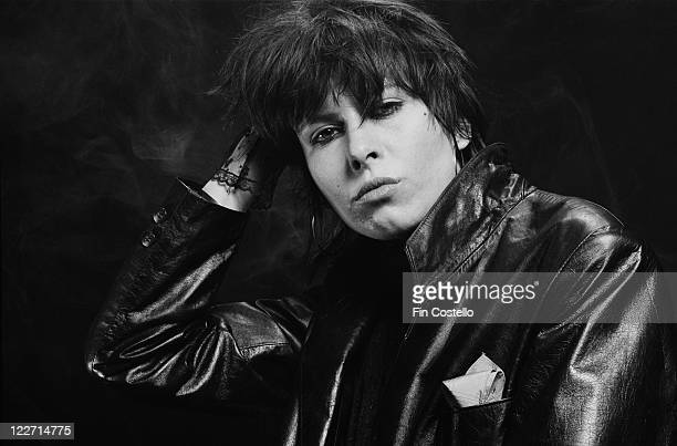 Chrissie Hynde US singer and guitarist with rock band The Pretenders wearing a black leather jacket in a studio portrait against a black background...