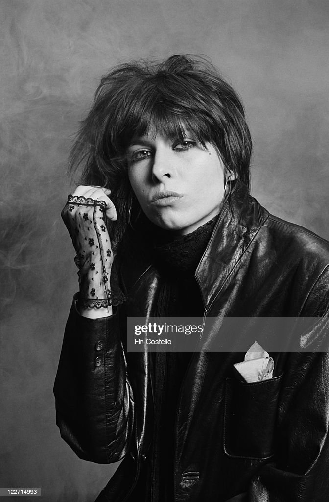 Chrissie Hynde, US singer and guitarist with rock band The Pretenders, wearing black lace fingerless gloves and a black leather jacket in a studio portrait, against a smoky background, United Kingdom, circa 1979.
