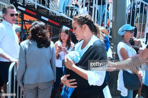 Chrissy Teigen holds her baby while walking past California Leiutenant Governor Gavin Newsom after she addressed the crowd on stage during a 'Familes...