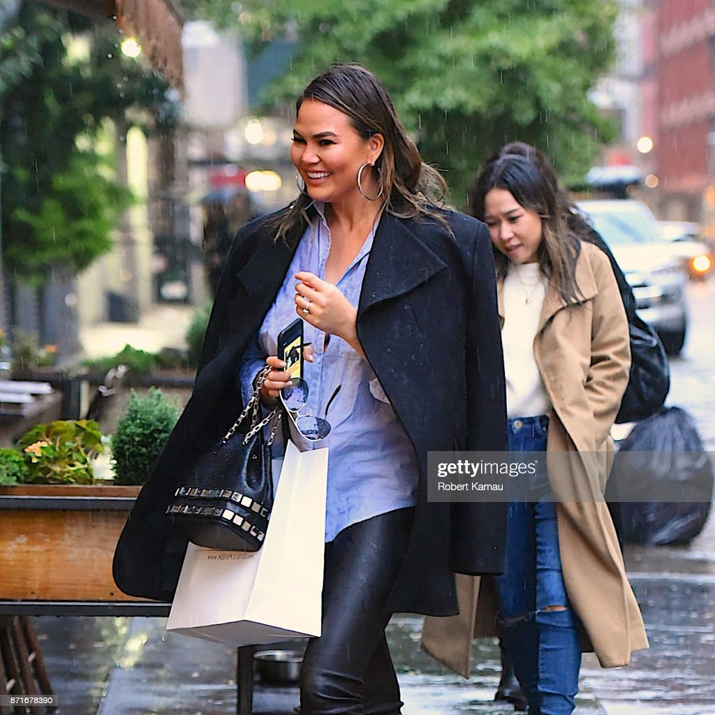 Chrissy Teigen smiled despite getting caught in the rain while shopping in Soho.