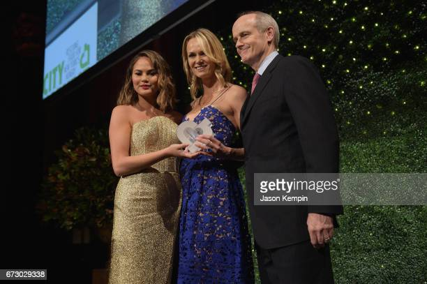 Chrissy Tiegen presents an award to Lise and Michael Evans onstage at the City Harvest's 23rd Annual Evening Of Practical Magic at Cipriani 42nd...