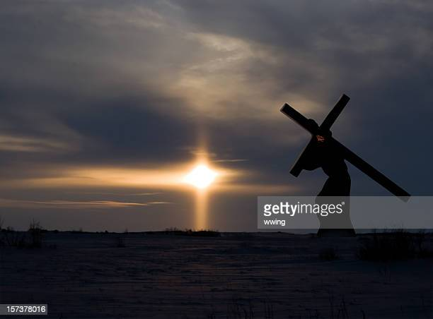 Christ carrying the cross with dark sunset