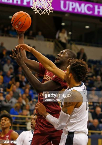 Christ Koumadje of the Florida State Seminoles and Terrell Brown of the Pittsburgh Panthers battle for the ball at Petersen Events Center on January...