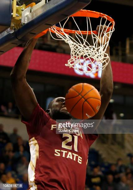 Christ Koumadje of the Florida State Seminoles dunks against Terrell Brown and Khameron Davis of the Pittsburgh Panthers at Petersen Events Center on...