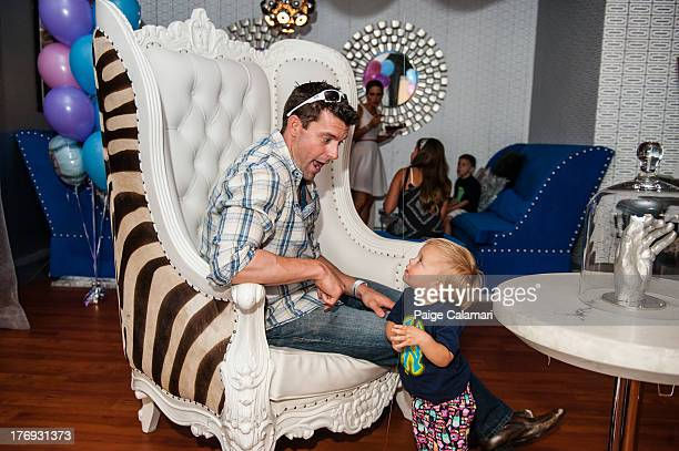 Christ Stewart of the New York Yankees plays with his daughter following the preview of the CCandy line during the CCandy Fashion Show at the MLB Fan...