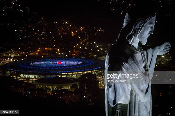 Christ the Redeemer statue is seen at sunset in front of the Maracana Stadium ahead of the 2016 Summer Olympic Games on July 31 2016 in Rio de...