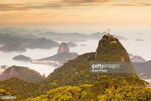 Christ the Redeemer statue on top of Corcovado mountain surrounded by Tijuca Forest and Sugar Loaf Mountain in background two of the most...