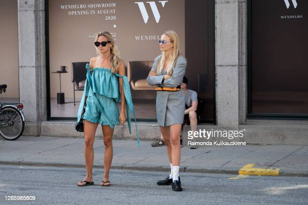 Christel Winther wearing Stine Goya electric green shorts and matching top and Hanni Gohr wearing grey blazer with belt and orange Carhartt outside...