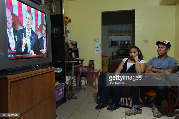 Christell Cayasso and Junior Perez watch on television as US President Barack Obama delivers his State of the Union speech to a joint session of the...