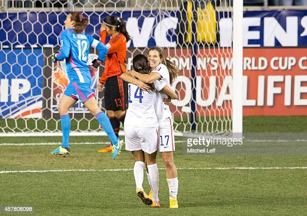 Christen Press and Tobin Heath of the United States react after Press scored a goal in the second of against Mexico in the 2014 CONCACAF Women's...
