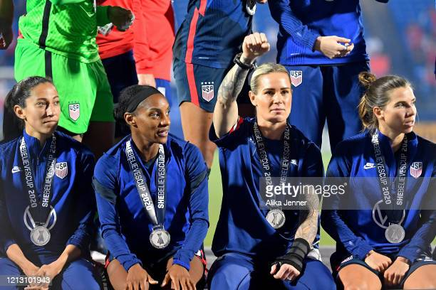 Christen Press of the United States Crystal Dunn Ashlyn Harris and Tobin Heath sit on the championship stage after the SheBelieves Cup match against...