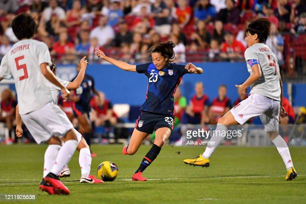 Christen Press of the United States kicks the ball under heavy pressure from Saki Kumagai and Moeka Minami of Japan during the first half of the...