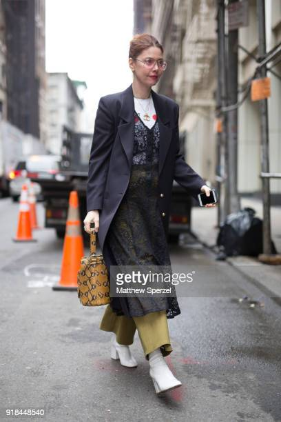Christene Barberich is seen on the street attending EDUN during New York Fashion Week wearing a long navy coat with lace dress on February 14 2018 in...