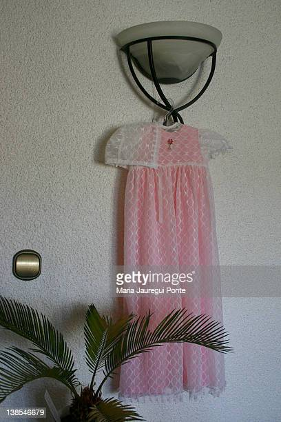 a christening gown hanging on a light fixture - christening gown stock pictures, royalty-free photos & images