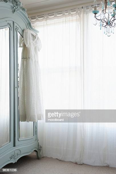 christening gown on wardrobe at window with net curtains - christening gown stock pictures, royalty-free photos & images