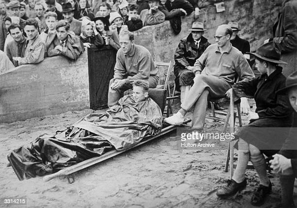 Christensen of Holland who broke his leg in heat 2 of the 800 metres at the 1948 London Olympics watches the athletics from a stretcher