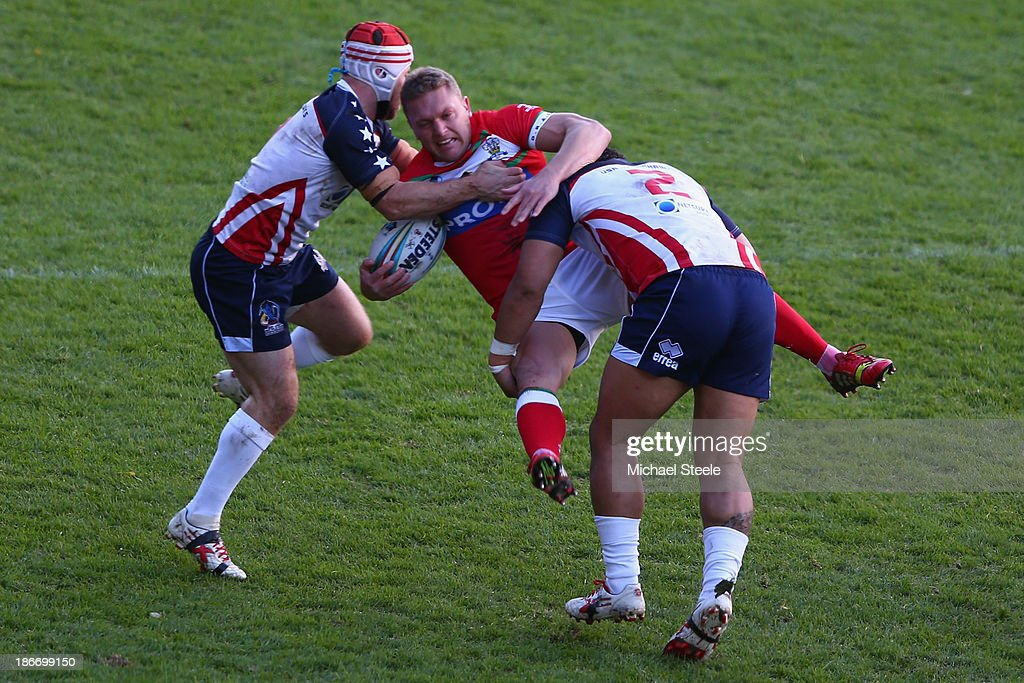 Christiaan Roets (C) of Wales is upended by Craig Priestly (L) and Bureta Faraimo (R) of USA during the Rugby League World Cup Group D match between Wales and USA at the Glyndwr University Racecourse Stadium on November 3, 2013 in Wrexham, Wales.