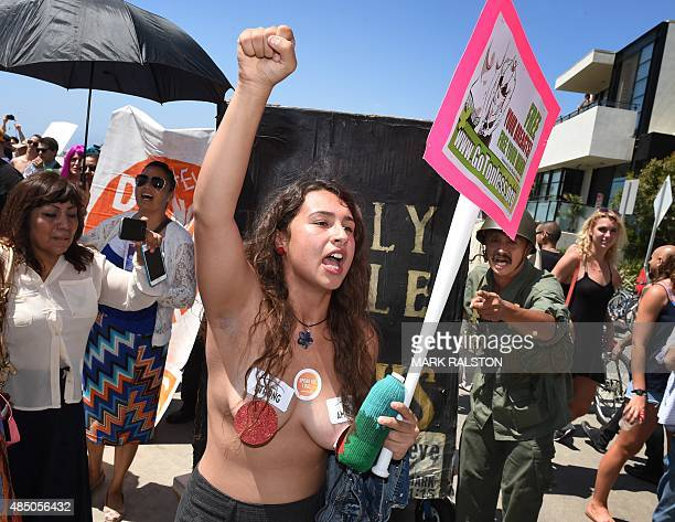 A Christian activist attempts to disrupt GoTopless Day protester Sharilynn Grace Krikl during their annual protest for women's rights in Venice Beach...