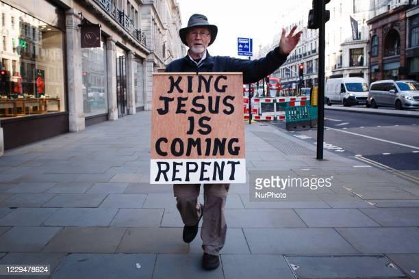 Christian activist wearing a sandwich board predicting the return of Jesus Christ walks along a near-deserted Regent Street in London, England, on...
