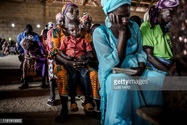 A Christian Adara boy prays along with his mother while attending the Sunday's service at Ecwa Church Kajuru Kaduna State Nigeria on April 14 2019...