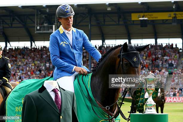 Christian Ahlmann of Germany rides on Codex One and the horse smells at the Rolex Grand Slam trophy after winning the Rolex Grand Prix jumping...