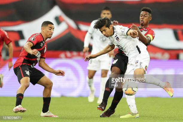 Christian and Wellington of Athletico Paranaense fight for the ball with Matias Fernandez of ColoColo during a group C match of Copa CONMEBOL...