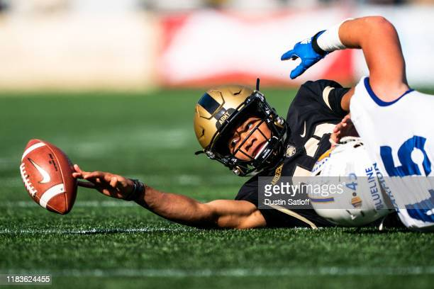 Christian Anderson of the Army Black Knights reaches to recover a fumble after being tackled by Kyle Harmon of the San Jose State Spartans during the...