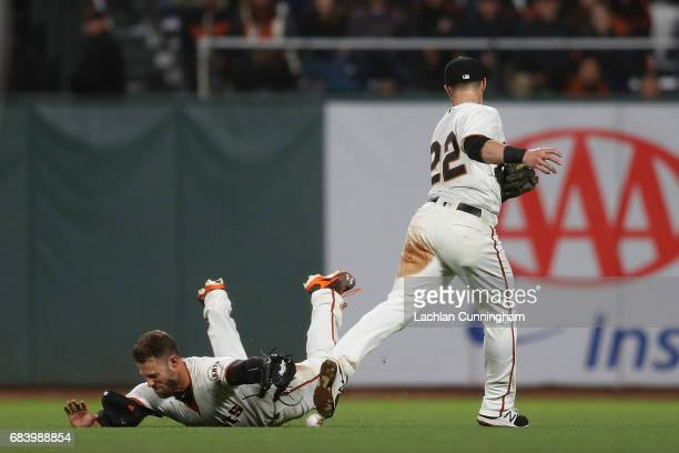Christian Arroyo and Mac Williamson of the San Francisco Giants fail to catch a fly ball hit by Justin Turner of the Los Angeles Dodgers at ATT Park...