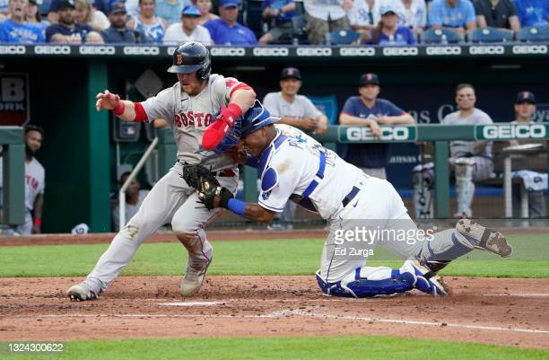Christian Arroyo of the Boston Red Sox is tagged out by Salvador Perez of the Kansas City Royals on a fielder's choice in the third inning at...