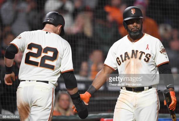 Christian Arroyo of the San Francisco Giants is congratulated by Denard Span after Arroyo scored against the Los Angeles Dodgers in the bottom of the...