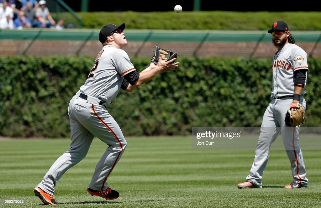 Christian Arroyo #22 of the San Francisco Giants makes a catch for an out against the Chicago Cubs as Brandon Crawford #35 looks on during the second inning at Wrigley Field on May 25, 2017 in Chicago, Illinois.