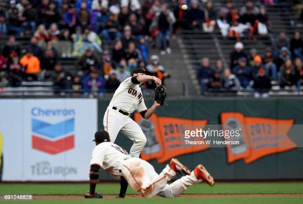 Christian Arroyo of the San Francisco Giants makes an off balance throw to first base but not in time to get Trea Turner of the Washington Nationals...