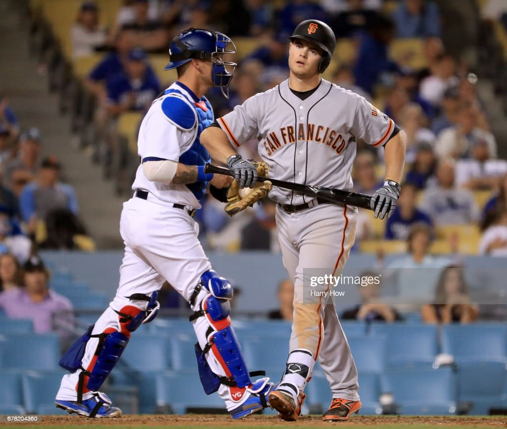Christian Arroyo #22 of the San Francisco Giants reacts to his strikeout with the bases loaded in front of Yasmani Grandal #9 of the Los Angeles Dodgers during the 10th inning at Dodger Stadium on May 3, 2017 in Los Angeles, California.