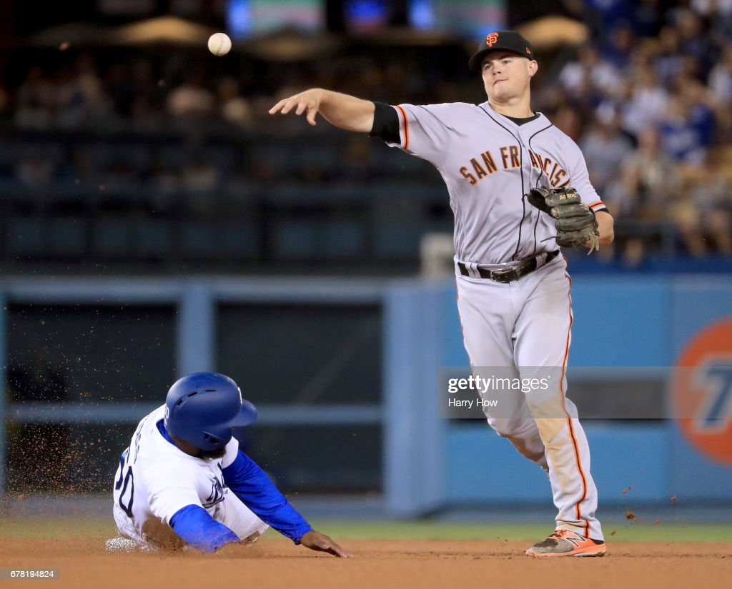 Christian Arroyo #22 of the San Francisco Giants turns a double play over Andrew Toles #60 of the Los Angeles Dodgers to end the ninth inning and send the game into extra innings at Dodger Stadium on May 3, 2017 in Los Angeles, California.