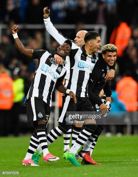 Christian Atsu, Ayoze Perez and DeAndre Yedlin of Newcastle United celebrate victory and promotion after the Sky Bet Championship match between...