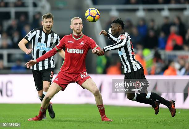 Christian Atsu of Newcastle United wins a header over Oliver McBurnie of Swansea City during the Premier League match between Newcastle United and...