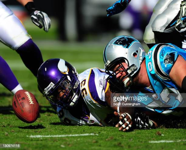 Christian Ballard of the Minnesota Vikings battles for a fumble against Geoff Hangartner of the Carolina Panthers at Bank of America Stadium on...