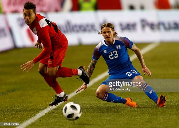 Christian Benavente of Peru fights for the ball with Ari Freyr Skúlason of Iceland during their friendly match at Red Bull Arena on March 27 2018 in...