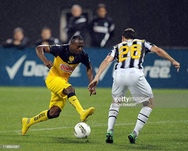 Christian Benitez of Club America moves the ball against Stephan Lichsteiner of Juventus during their Herbalife World Football Challenge match on...