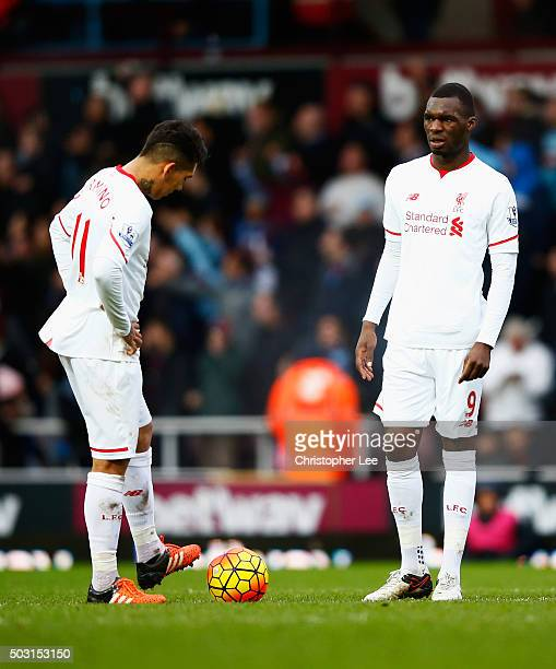 Christian Benteke and Roberto Firmino of Liverpool react after West Ham's second goal during the Barclays Premier League match between West Ham...