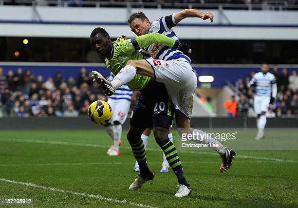 Christian Benteke of Aston Villa and Clint Hill of Queens Park Rangers battle for the ball during the Barclays Premier League match between Queens...