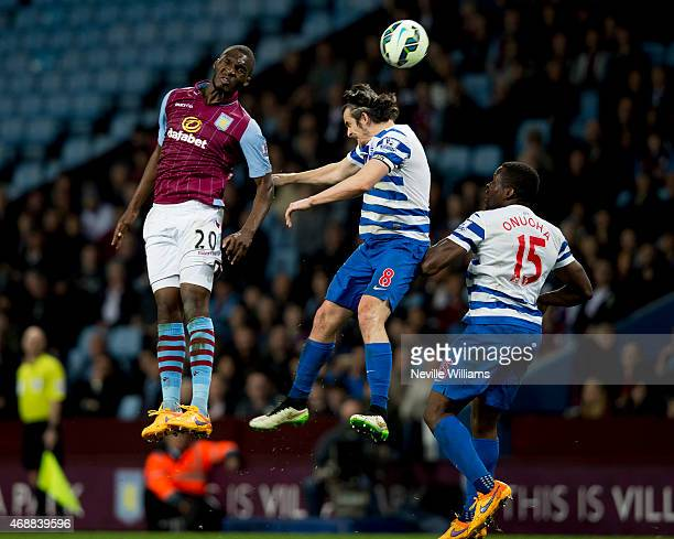 Christian Benteke of Aston Villa is challenged by Joey Barton of Queens Park Rangers during the Barclays Premier League match between Aston Villa and...