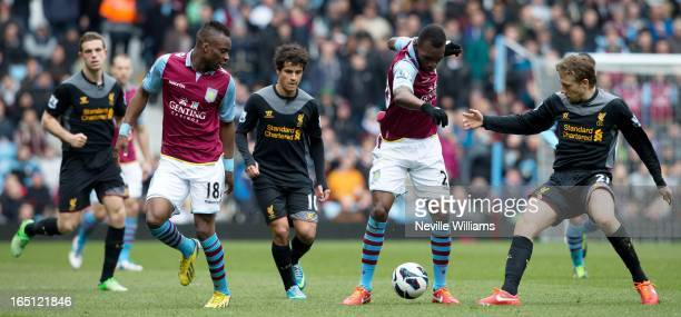 Christian Benteke of Aston Villa is challenged by Lucas Leiva of Liverpool as Yacouba Sylla of Villa and Philippe Coutinho look on during the...