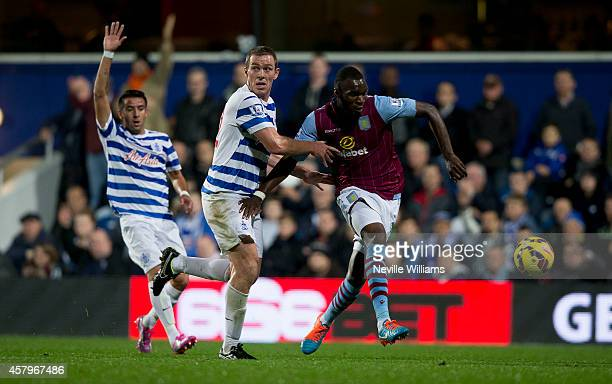 Christian Benteke of Aston Villa is challenged by Richard Dunne of Queens Park Rangers during the Barclays Premier League match between Queens Park...