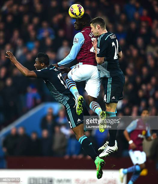 Christian Benteke of Aston Villa jumps for the ball with Mikel John Obi and Gary Cahill of Chelsea during the Barclays Premier League match between...