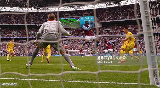Christian Benteke of Aston Villa scores their first goal past Simon Mignolet of Liverpool during the FA Cup Semi Final between Aston Villa and...