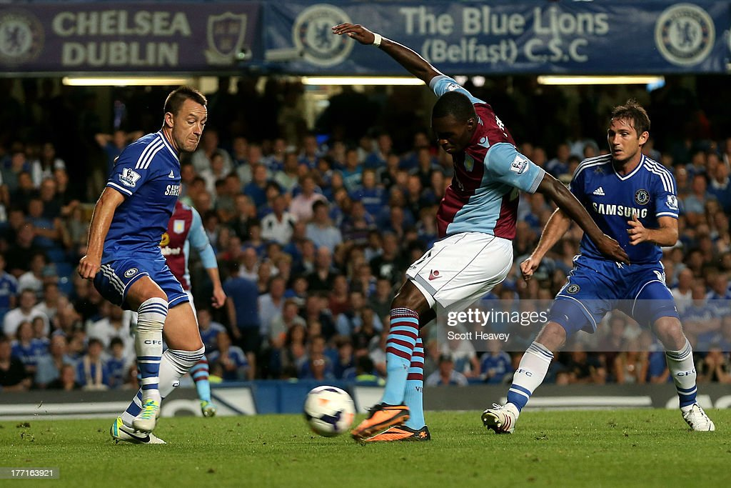 Christian Benteke of Aston Villa shoots past John Terry of Chelsea to score a goal to level the scores at 1-1 during the Barclays Premier League match between Chelsea and Aston Villa at Stamford Bridge on August 21, 2013 in London, England.